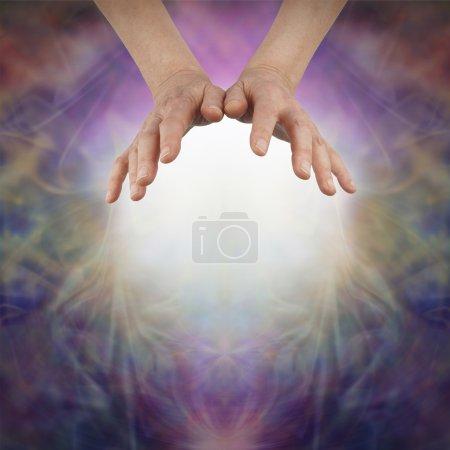 Photo pour Les mains de femelle en vol stationnaire au-dessus d'une boule de lumière blanche sur une très belle énergie brumeux richement colorés formation fond et copie espace ci-dessous - image libre de droit