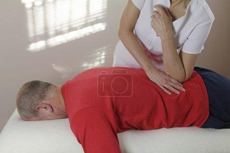 Massage therapist pressing elbow into sportman's Q...