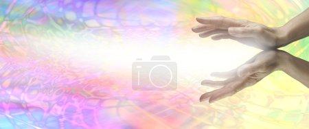 Photo pour Les mains tendues du guérisseur avec l'énergie rayonnant vers l'extérieur sur un fond psychédélique arc-en-ciel - image libre de droit