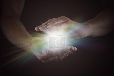 Photo pour Mains masculines émergeant de l'obscurité, coupées, avec arc-en-ciel couleur éclat d'étoile blanche brillante de la lumière entre - image libre de droit