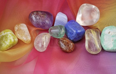 Close up of chakra gemstones on rainbow colored chiffon material