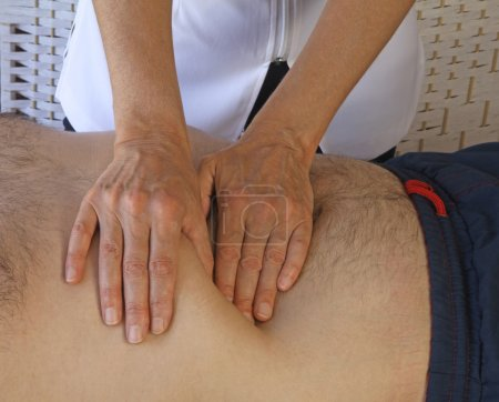 Photo for Female therapist performing abdominal examination on male torso - Royalty Free Image