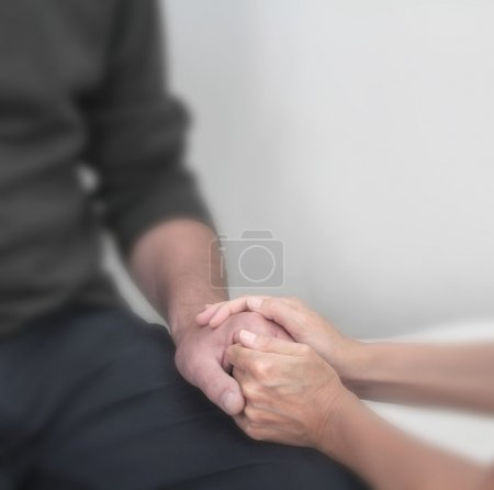 Foto de Cropped image focusing on therapist holding client's hand offering comfort with a soft blur effect on everything except the hands. - Imagen libre de derechos