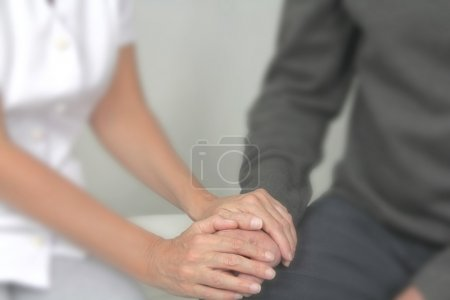 Photo pour Therapist holding male client's hand offering comfort with a soft blur effect on everything except the hands. - image libre de droit