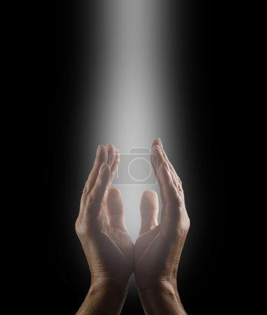 Photo pour Mains masculines atteignant vers le haut dans un jet de lumière blanche priant l'Esprit Divin sur un fond noir - image libre de droit