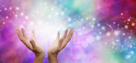 Photo pour Mains ouvertes étendues sur un fond large rose et bleu étincelant magique bokeh - image libre de droit