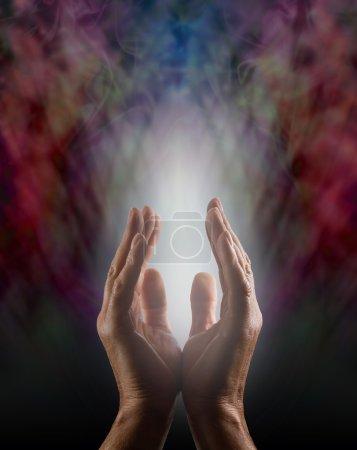 Photo pour Les mains parallèle mâle atteignant en un faisceau de lumière blanche sur un fond noir avec un descendant d'énergie brume éthérée - image libre de droit