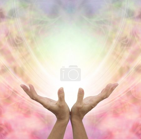 Photo for Female hands outstretched sensing a beautiful pastel colored Angelic energy field with a ball of white light at the center and plenty of copy space around - Royalty Free Image
