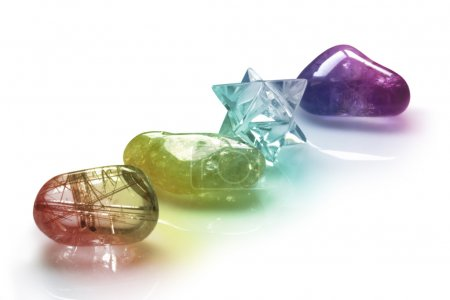 Photo pour Four rainbow colored healing crystals in a row on a white background - image libre de droit