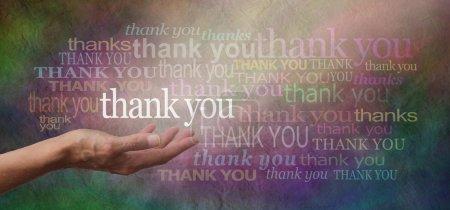 """Photo pour Main féminine tendue avec le mot """"merci"""" flottant ci-dessus, entourée de nombreux mots de remerciement de couleur différente sur un large fond d'effet de pierre rustique multicolore et un arbre de lumière brillant sur le remerciement principal - image libre de droit"""