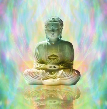 Photo pour Statue de Bouddha dans la position de lotus sur une surface réfléchissante avec un fond éthéré multicolore d'énergie - image libre de droit