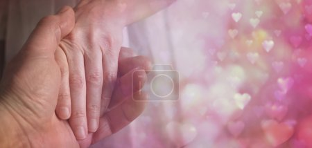 Photo for Wide soft focus cropped image of a man holding a woman's hand tenderly with  love hearts floating around on right hand side and plenty of copy space - Royalty Free Image