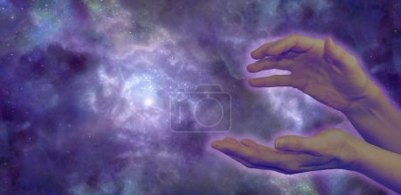 Photo pour Wide night sky background, showing a nebula in outer space with a women's hands in the foreground in a sensing energy position, with pale lilac aura and plenty of copy space - image libre de droit