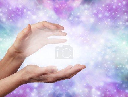Photo pour Mains féminines en position de détection d'énergie avec une boule de lumière brumeuse blanche entre sur un fond bleu pailleté scintillant et violet pastel - image libre de droit