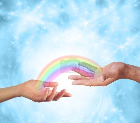 Photo pour Main femelle faisant vers le haut et main masculine faisant face vers le haut avec un arc-en-ciel transparent les reliant ensemble sur un fond bleu étincelant de formation d'énergie - image libre de droit