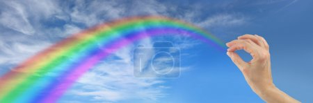 Photo pour Grand ciel bleu avec des nuages duveteux et une main féminine qui semble toucher l'extrémité lointaine d'un arc-en-ciel qui vole dans le ciel comme s'il l'envoyait - image libre de droit