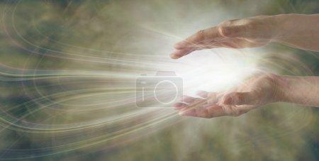 Photo pour Paire de mains parallèles de guérisseuse avec une formation complexe d'énergie lumineuse blanche entre sur un large fond doré muet avec beaucoup d'espace de copie - image libre de droit