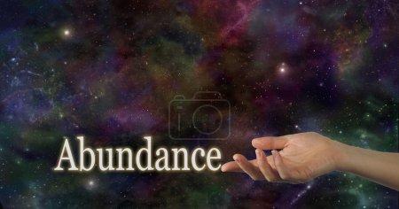 Photo pour Main femelle faisant face vers le haut avec l'abondance de mot touchant l'index sur un fond de ciel de nuit d'espace profond fournissant l'abondance de l'espace de copie au-dessus - image libre de droit