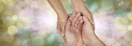 Photo pour Grande bannière avec une main féminine tenant une main coupée mâle dans un geste nécessiteux sur un fond de bokeh et de lumière éclatée et beaucoup d'espace de copie de chaque côté - image libre de droit