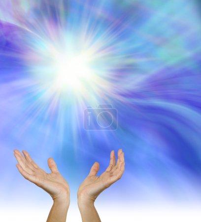 Photo pour Mains de guérison femelle tendues vers le haut vers une étonnante formation d'étoiles blanches sur un fond de champ d'énergie bleu - image libre de droit