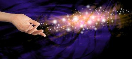 Photo pour Femme main tendue avec un jet d'étincelles flottant loin sur un fond tourbillonnant bleu foncé - image libre de droit