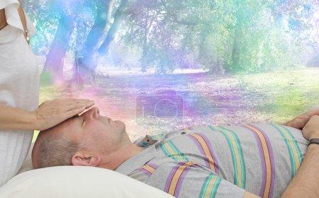 Photo pour Praticien de guérison détectant l'énergie du client masculin couché couché couché sur le canapé avec un fond coloré de bokeh arc-en-ciel fantaisie - image libre de droit