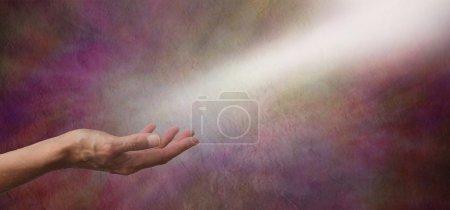 Photo pour Femme main vers le haut, avec un arbre de lumière blanche venant du haut à droite semblant toucher la paume comme si reçoit, sur une bannière de fond rouge vermeil effet pierre - image libre de droit
