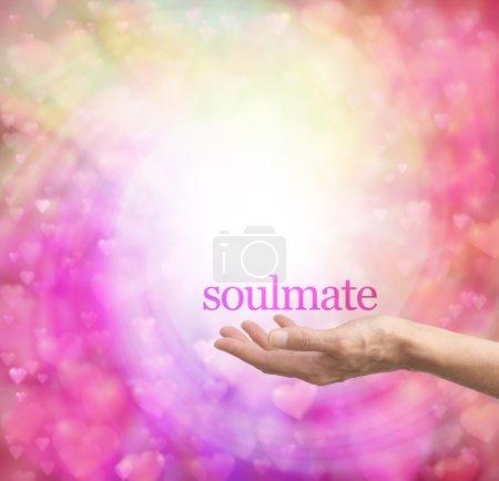 Photo pour Paume de main féminine vers le haut avec le mot âme soeur flottant au-dessus, entouré d'une spirale de coeurs amour flou de couleur pastel sur un fond de bokeh - image libre de droit