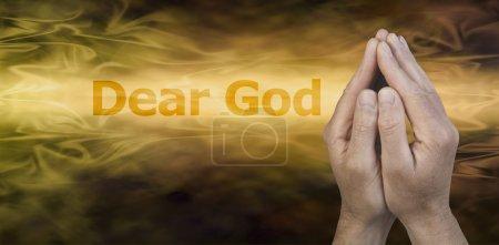 Photo pour Mains masculines en position de prière sur un fond de streaming doré avec les mots Cher Dieu à gauche et beaucoup d'espace de copie sous - image libre de droit