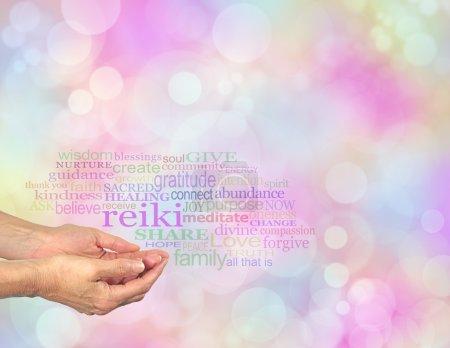 Photo pour Mains femelles concave avec le mot « Reiki » flottant au-dessus, entouré d'un nuage de mot guérison pertinentes sur un pastel bokeh fond de couleur - image libre de droit