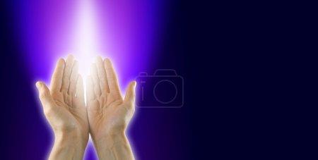 Photo pour Female guérisseur à mains ouvrent face à palm et un puits de lumière blanche entourée d'énergie magenta et violette sur fond noir et blanc avec beaucoup d'espace de copie - image libre de droit