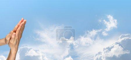 Photo pour Femme les mains en position de prière sur un fond de ciel bleu large magnifique avec beaucoup d'espace de copie - image libre de droit
