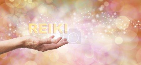 Photo pour Femelle avec la main tendue paume vers le haut et le mot « Reiki » planant au-dessus sur une éthérée bokeh et miroite fond et blanc lumière dorée - image libre de droit