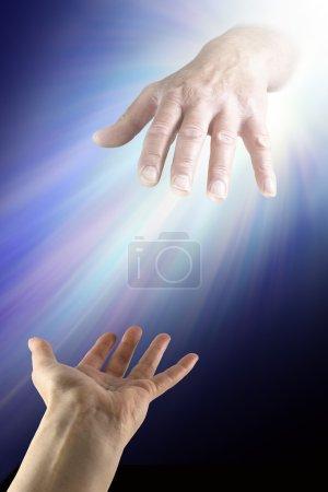 Photo pour Une main féminine avec paume ouverte atteignant une main masculine rougeoyante qui sortent d'un éclairage nouveau sur un fond sombre - image libre de droit