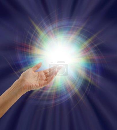 Photo pour Main ouverte tendue vers le haut dans une boule multicolore de lumière blanche en spirale sur un fond de formation d'énergie sortante bleu indigo foncé - image libre de droit
