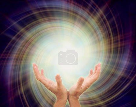 Photo pour Les mains ouvertes taillées vers une étoile dorée émergeant d'une formation spirale multicolore sur un fond bleu indigo foncé représentant l'inspiration divine - image libre de droit