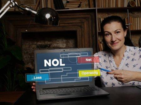 Photo pour Femme d'affaires au travail avec des rapports financiers NOL perte nette d'exploitation et un lapto - image libre de droit