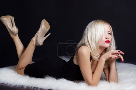 Beautiful sexy elegant striking blonde woman with bright makeup red lips in a black dress lies on the white fur in the Studio on a black background
