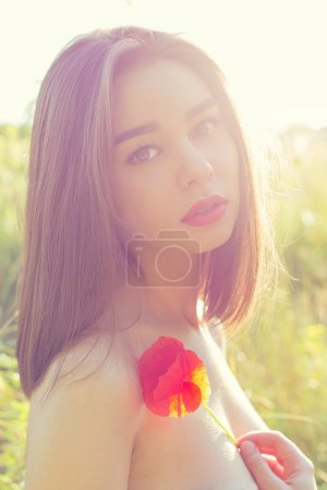beautiful sexy girl with plump lips with a poppy flower in the hand with bared shoulders at sunset in a field in the sunlight , shading in warm colors