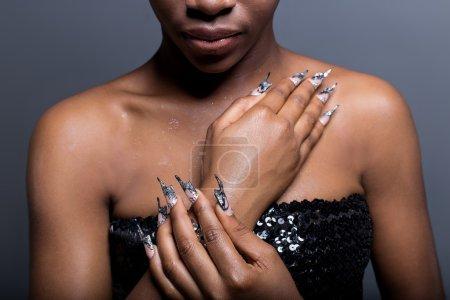 Photo pour Belle main de la jeune fille à la peau foncée sur les épaules de prothèse d'ongles en acrylique avec clou fotmoy insolite - image libre de droit