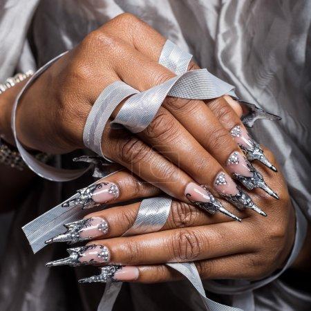 Photo pour Belle main de la jeune fille avec greffe de peau foncée des ongles en acrylique avec clou fotmoy insolite - image libre de droit