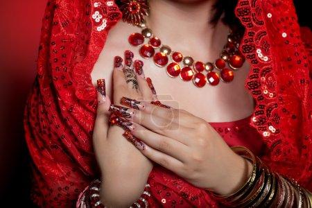 Photo pour Belle fille à l'image de la femme indienne dans un sari rouge avec de beaux ongles en acrylique patch dans le style oriental dans le studio - image libre de droit