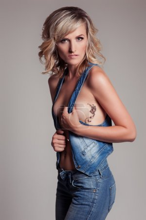 beautiful sexy woman in blue jeans and a waistcoat with a tattoo on the side of a bird hummingbird in the studio