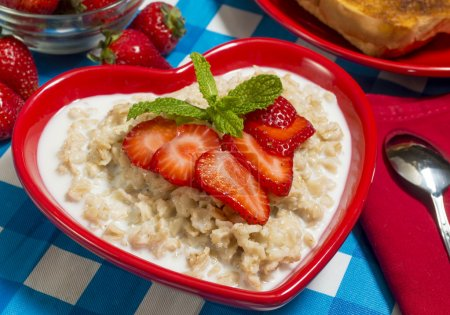 Photo for Bowl of hot oatmeal served with fresh strawberries and toast - Royalty Free Image