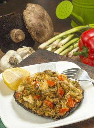 Crab stuffed portobello mushroom set on serving pl...