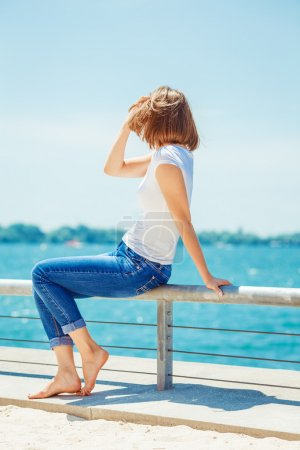 girl woman in jeans sitting near water