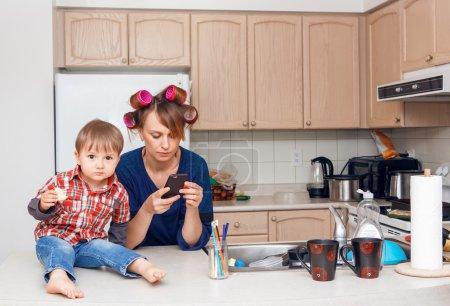 Photo pour Occupé blanc caucasien jeune femme mère femme au foyer avec bigoudis dans les cheveux, prendre des photos des objets, les objets, les ustensiles dans sa cuisine, son enfant enfant fils garçon assis à côté de son manger un cookie, souriant et en jouant, folle vie bien remplie - image libre de droit