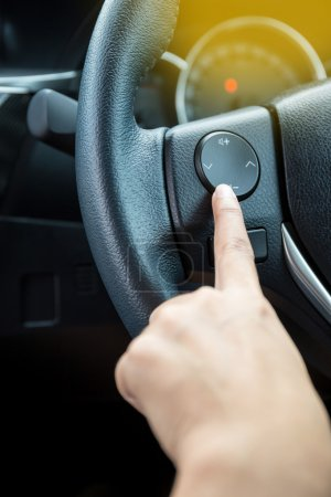 A woman hand pushes the volume control button on a steering whee
