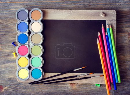 Photo pour Tableau noir avec crayons de couleur, palette, aquarelle aquarelle pour la peinture et le dessin, espace de copie, concept de créativité et d'apprentissage, fond rustique - image libre de droit