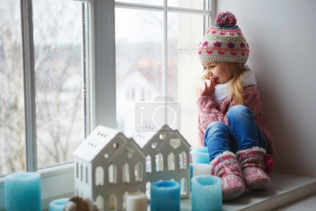 Photo for Little girl on a window sill looks at the street - Royalty Free Image